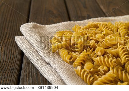 Dark Yellow Raw Whole Grain Pasta With Bran On Linen Cloth And Wooden Background