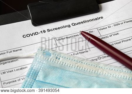Covid-19 Screening Questionnaire Form With Medical Mask And A Pen On It. Healthcare And Medical Conc