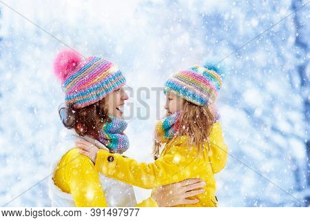 Mother And Child In Knitted Winter Hats Play In Snow On Family Christmas Vacation. Handmade Wool Hat