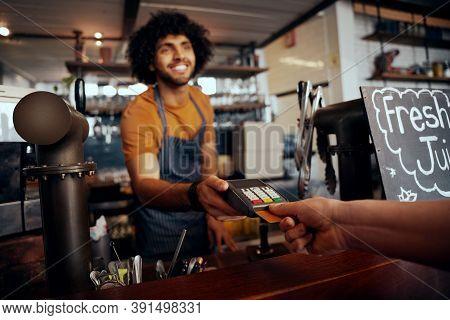 Waiter Holding Credit Card Swipe Machine While Customer Typing Code In Modern Cafe