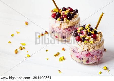 Overnight Oatmeal With Berries And Nuts In A Jar On A White Background. Healthy Breakfast Concept.