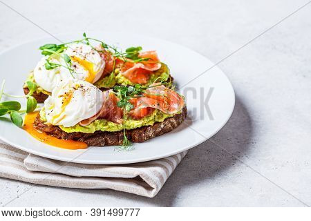 Toast With Salmon, Poached Egg And Avocado On A White Plate. Poached Egg With Salmon And Guacamole O