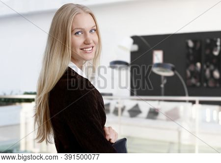 Happy young businesswoman looking back over the shoulder smiling at camera.