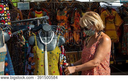 A Woman With Face Mask Is Shopping Clothes