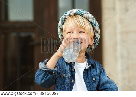 Cute Little Boy Drinking Water From The Plastic Bottle. Child Drinks Water Outdoor. Kid Drinking Min