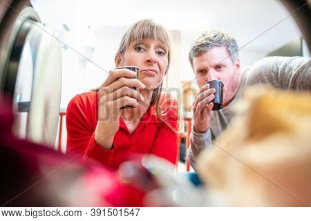 man and woman look into a laundry drum with coffee cups in their hands waiting for their laundry
