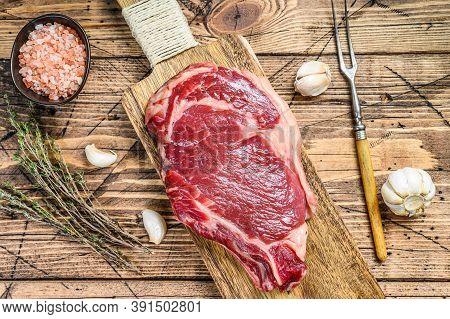 Raw Rib Eye Steak On The Bone. Marble Beef Meat Ribeye. Wooden Background. Top View