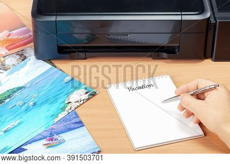 Man Planning Vacation With  Photos He Printed After Summer Vacation. Concept Planning Summer Vacatio