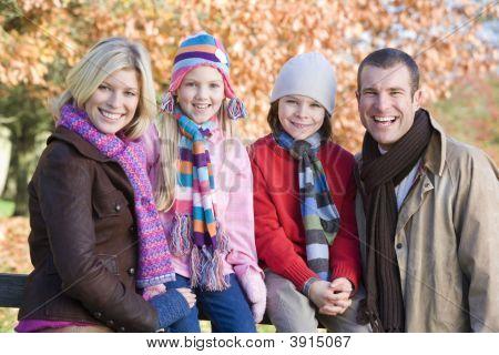 Family Sat On Woodland Fence