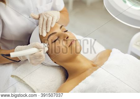 Cosmetologist Making Vacuum Facial Skin Cleaning For Young Woman In Beauty Salon
