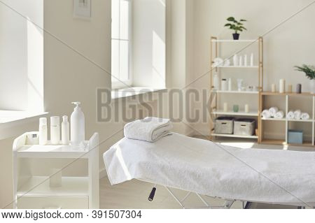 Massage Room Or Beauty Parlor With Empty Bed And Ready Set Of Organic Skincare Products