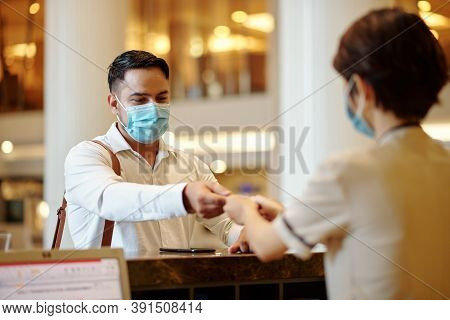 Hotel Receptionist Giving Digital Room Key To Guest In Medical Mask