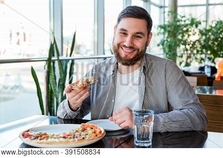 Portrait Happy Smiling Caucasian Man Eating Italian Pizza In Pizzeria Keeps Social Distance. Delicio