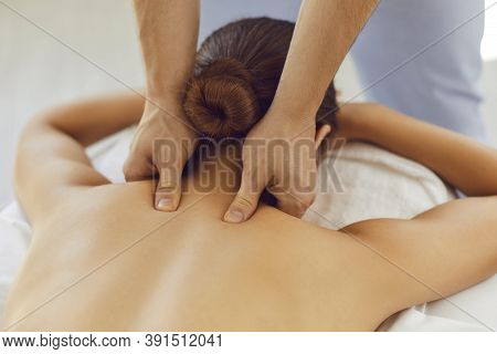Mens Hands Do A Therapeutic Neck Massage For A Girl Lying On A Massage Couch In A Massage Spa.