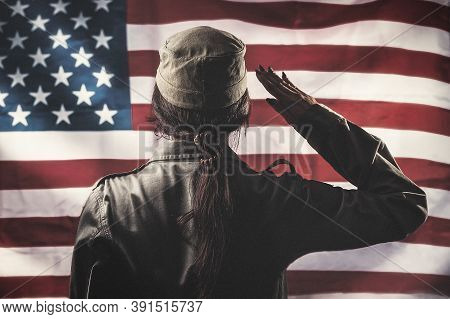 Veterans Day, Memorial Day, Independence Day. A Female Soldier Saluting, Against The Background Of T