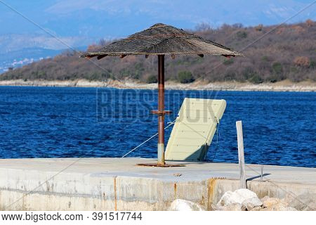 Wicker Beach Parasol With Rusted Wire On Top Mounted On Thick Metal Pole On Top Of Concrete Pier Nex