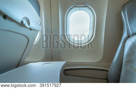 Plane Window With White Sunlight. Empty Plastic Airplane Tray Table At Seat Back. Economy Class Airp