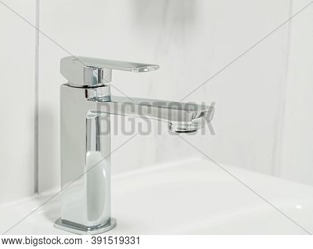 New Metal Shiny Valve Square Sink Faucet With Feflections In White Interior. Close-up. Macro