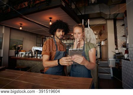 Young Serious Co-workers Using Digital Tablet While Standing In Modern Cafe