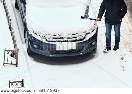 Person Removes Snow From The Car In Winter On The Street.