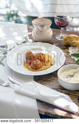 Polenta With Meatballs In Tomato Sauce. Traditional Italian Pork And Beef Meatballs Served On Polent