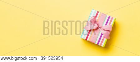 Wrapped Christmas Or Other Holiday Handmade Present In Paper With Pink Ribbon On Yellow Background.