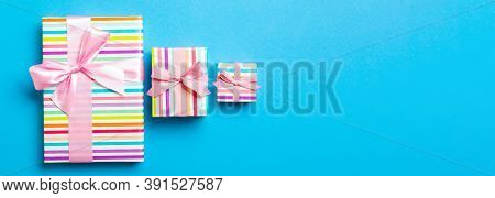 Wrapped Christmas Or Other Holiday Handmade Present In Paper With Pink Ribbon On Blue Background. Pr