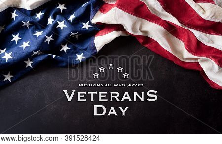Happy Veterans Day Concept. American Flags Against A Dark Stone  Background. November 11.