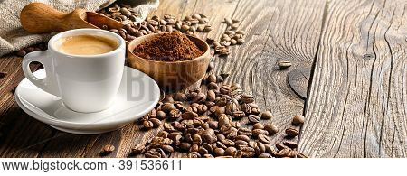 Coffee Cup And Beans On Old Wooden Table With Coffee Powder And Wooden Scoop. Copy Space