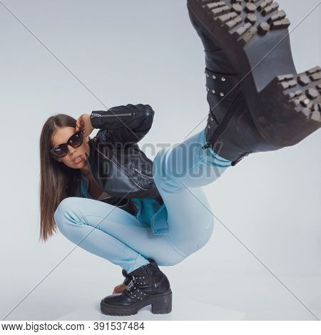 Tough fashion model holding sunglasses and kicking with her leg, crouching on gray studio background