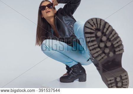 Charming fashion model adjusting sunglasses and kicking with her leg, crouching on gray studio background
