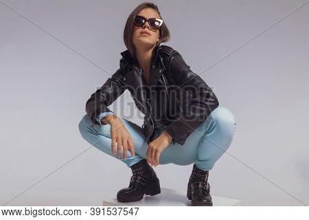 Charming fashion model wearing leather jacket and sunglasses, crouching on gray studio background