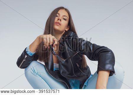 Charming fashion model taking off sunglasses, wearing leather jacket, crouching on gray studio background
