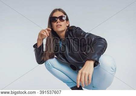 Surprised fashion model gasping while wearing sunglasses and leather jacket, crouching on gray studio background