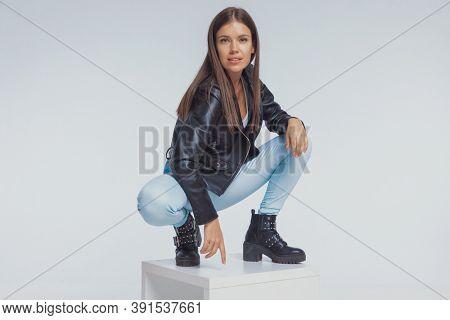 Confident fashion model smiling, wearing leather jacket while crouching on gray studio background