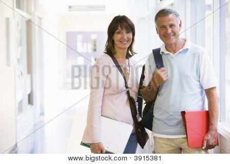 Man And Woman Stood In School Corridor