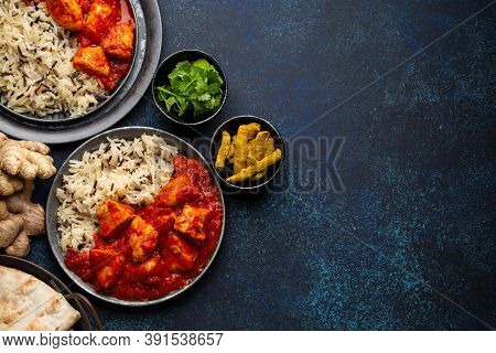 Chicken Tikka Masala Dish With Rice, Flat Indian Bread And In Rustic Metal Plates On Concrete Backgr