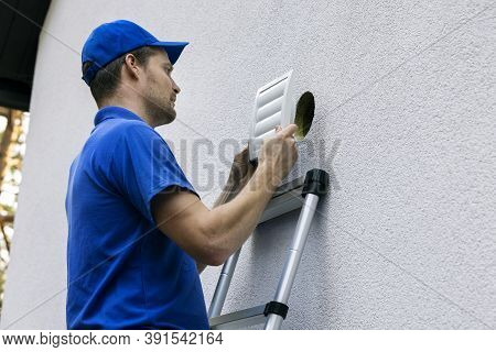 Home Ventilation - Hvac Worker Standing On Ladder And Installing Air Duct Grille On House Facade