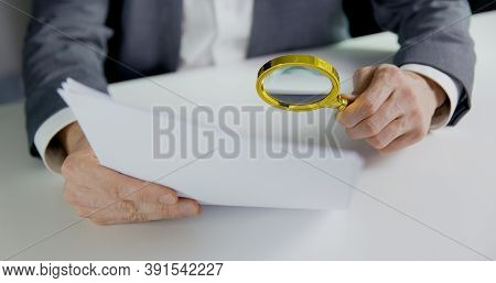 Businessman Or Auditor Inspecting Document With Magnifying Glass In Office. Business Financial Audit