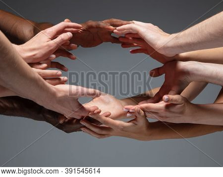 Save. Hands Of Peoples Crows In Touch Isolated On Grey Studio Background. Concept Of Human Relation,