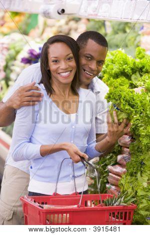 Couple Choosing Vegetables In Shop