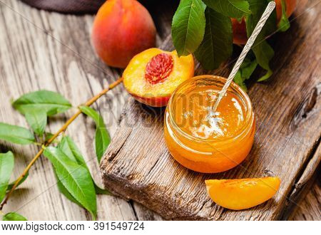 Peach Jam In Glass Jar With Wedges And Whole Peach Fruit, Peach Tree Leaves. Peach Jam On A Wooden T