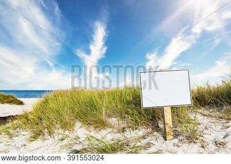 Signpost With Copy Space On Wide Sandy Beach Against Sea And Blue Sky