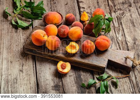 Peaches With Leaves On Wooden Table With Peach In Halves. Ripe Juicy Peaches. Harvest Of Peaches For