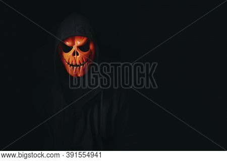 Man In Spooky Pumpkin Skull Cosplay In Black Dressed For Halloween Festival On Black Background