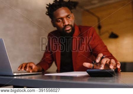 Black Business Man Counts On A Calculator And Makes Notes. Financier Or Accountant Works From Home