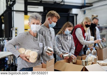 Group Of Volunteers In Community Charity Donation Center, Food Bank And Coronavirus Concept.