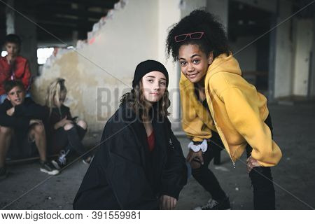 Group Of Teenagers Girl Gang Standing Indoors In Abandoned Building, Hanging Out.