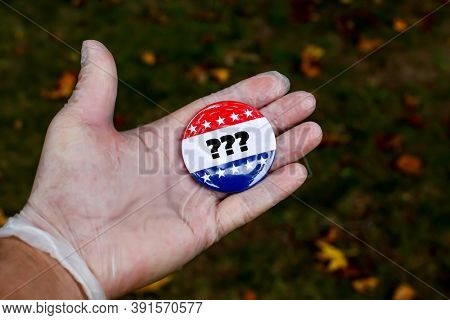 Hand with protective glove showing vote pin with questins mark