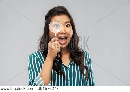 investigation, discovery and vision concept - happy asian woman looking through magnifying glass over grey background
